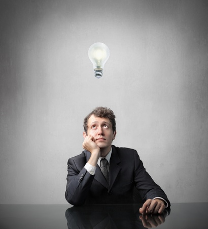 minds: Businessman with thoughtful expression with light bulb over his head