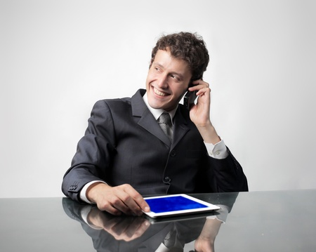 Smiling businessman talking on the mobile phone while using a tablet pc Stock Photo - 10223446