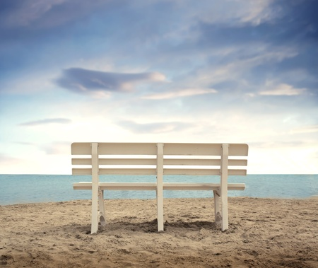 sitting on a bench: Wooden bench in front of the sea