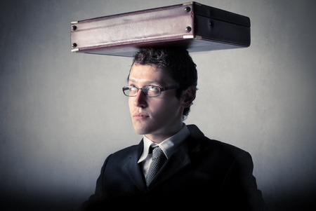 burdensome: Businessman holding a thick book on his head Stock Photo