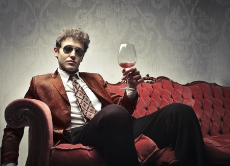 Elegant man sitting on a velvet sofa and holding a glass of wine