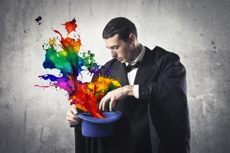Goochelaar gekleurde verf extraheren uit zijn hoed cilinder Stockfoto