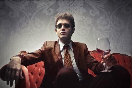 金持ち: ワインのガラスを保持してエレガントな若い男