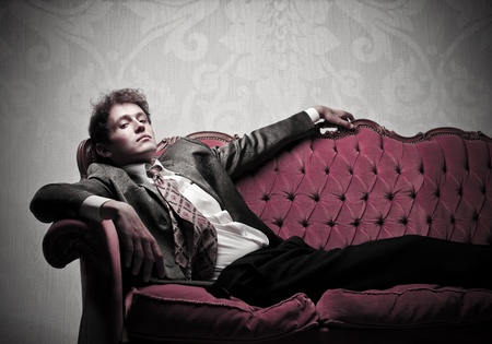 red sofa: Handsome elegant young man lying on a velvet sofa