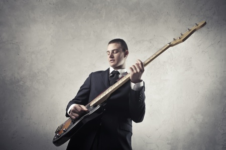 young musician: Businessman playing guitar