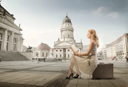 street fashion: Beautiful woman sitting on a suitcase and reading a book with monument in the background