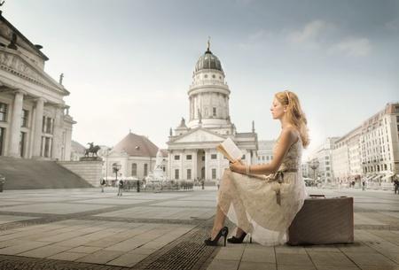 mujer leyendo libro: Hermosa mujer sentada en una maleta y leyendo un libro con monumento en segundo plano Foto de archivo