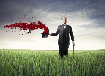 magic show: Magician on a green meadow with red paint coming out of his hat Stock Photo
