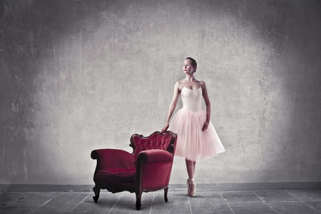 beside: Ballerina standing beside an armchair Stock Photo