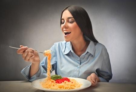 pasta fork: Happy woman eating pasta Stock Photo