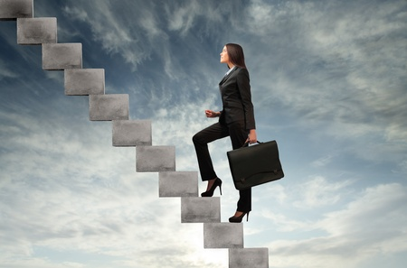 steps to success: Businesswoman stepping up a staircase with sky in the background