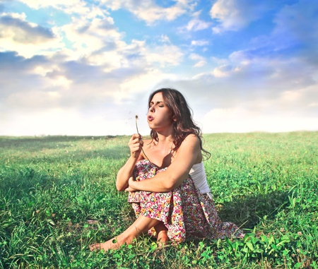 Beautiful woman blowing out a dandelion on a green meadow photo