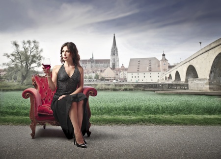 Beautiful elegant woman sitting on an armchair and drinking a glass of wine with antique village in the background photo