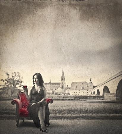 mujer elegante: Hermosa mujer elegante sentado en un sillón y beber un vaso de vino con la antigua aldea en segundo plano