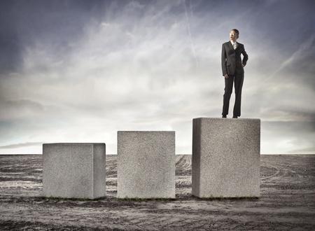 presumption: Businesswoman standing on a high cube on a desert