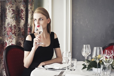 sitting at table: Beautiful woman sitting at a luxury restaurant table and having a glass of water Stock Photo