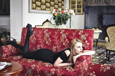 Beautiful woman lying on a sofa in a luxury hotel photo