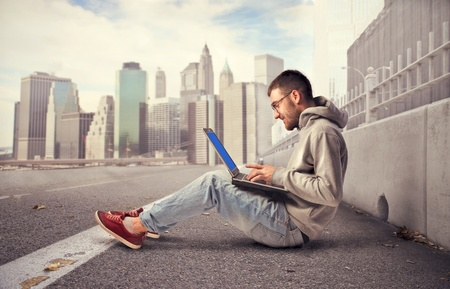 Young man sitting on a city street and using a laptop photo