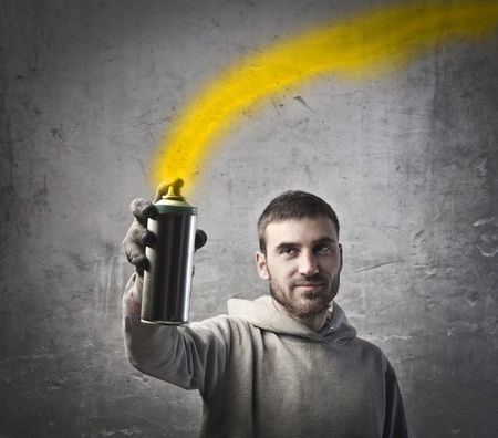 spray can: Young man spraying yellow paint Stock Photo