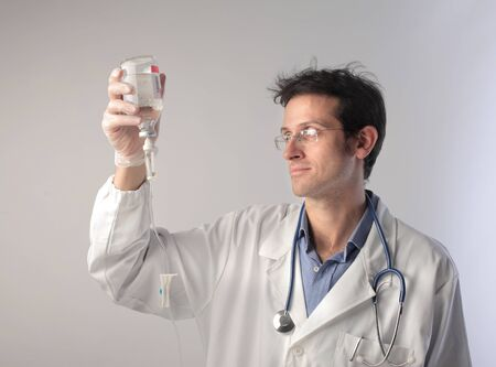 Doctor checking the content of a drip Stock Photo - 10805093