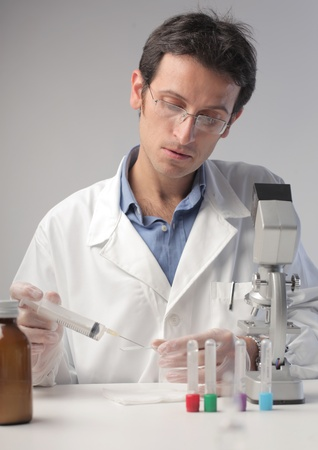 Doctor putting a solution from a test tube onto a slide Stock Photo - 10805091