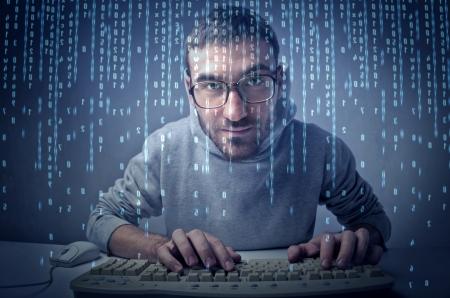 Junger Mann das Tippen auf einer Computer-Tastatur vor einem Bildschirm