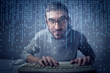 hackers: Young man typing on a computer keyboard in front of a screen