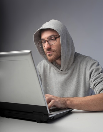 Young hacker using a laptop photo