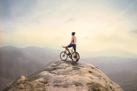 cyclist: Fietser op een piek in de bergen