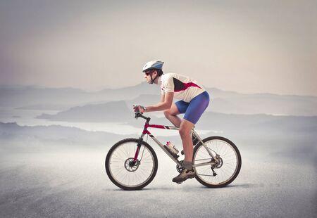 ciclista: Ciclista montado en su bicicleta en un desierto Foto de archivo