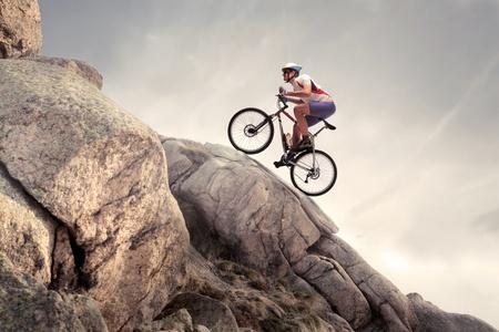 montando bicicleta: Ciclista subiendo una roca con su bicicleta de monta�a Foto de archivo