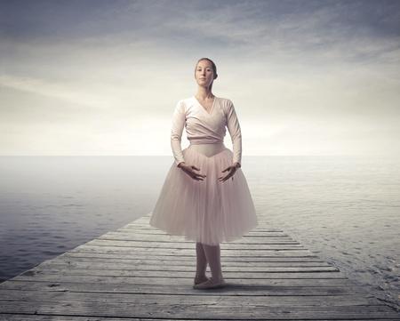 ballet clásico: Hermosa bailarina en un muelle sobre un lago Foto de archivo