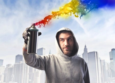 graffiti art: Young man spraying colored paint with cityscape in the background Stock Photo