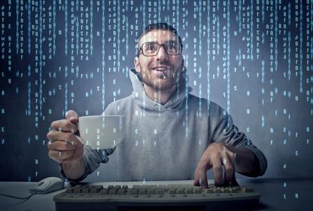friki: Sonriente a joven sentado frente a una pantalla de ordenador y la celebraci�n de una taza de caf� Foto de archivo