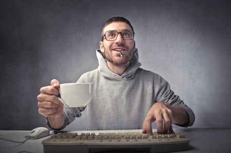 nerd glasses: Smiling young man using a computer and holding a cup of coffee