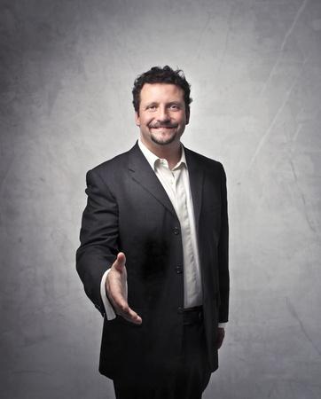 scoundrel: Affari sorridente tendendo la mano a qualcuno