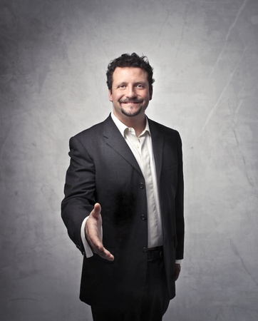 trust people: Smiling businessman holding out his hand to somebody