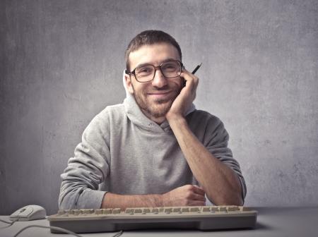 friki: Sonriente a joven ma sentado delante de un teclado de computadora
