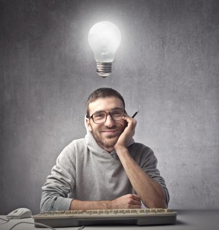 그의 머리에 전구 컴퓨터 앞에 웃 고 젊은 남자