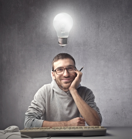 light bulb idea: Smiling young man in front of a computer with light bulb over his head