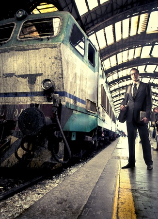 pendular: Businessman standing on a platform beside a train