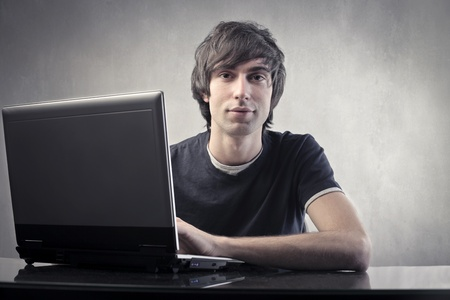 Young man using a laptop Stock Photo - 10905293
