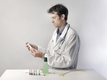 Doctor doing a test with a syringe and some test tubes Stock Photo - 10905142