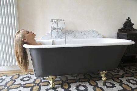 bathtub: Beautiful woman lying in a bathtub