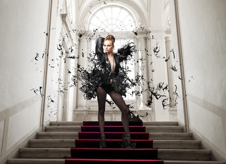 undress: Beautiful woman on a staircase with her dress explosing in black paint Stock Photo