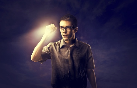 obscured: Young man lighting the dark with a torch Stock Photo