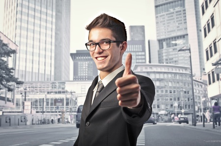 Smiling businessman with thumbs up and cityscape in the background