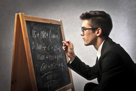 Businessman writing some calculations on a blackboard
