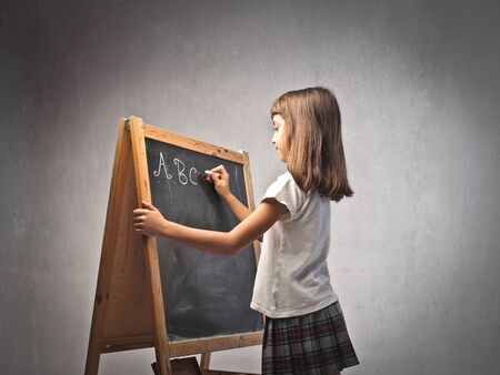 Little girl writing the alphabet on a blackboard photo