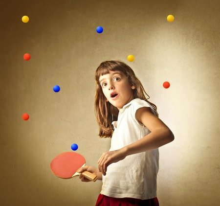 ping pong: Little girl playing ping pong with many balls Stock Photo